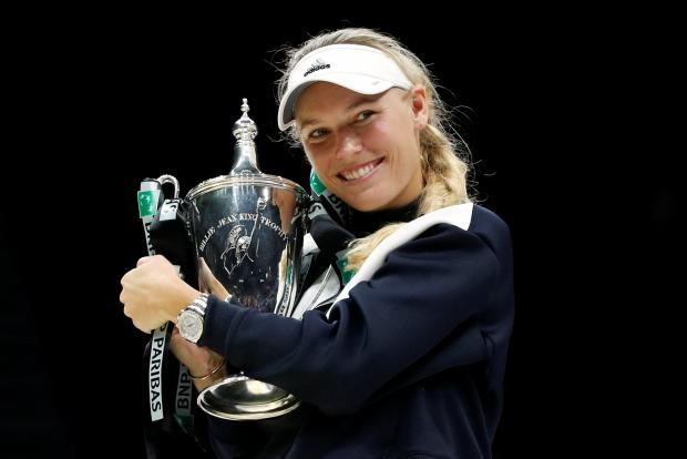 Denmark's Caroline Wozniacki celebrates with the trophy after winning the final against USA's Venus Williams.