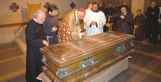 Archbishop Domenico D'Ambrosio opening the coffin of Padre Pio after the saintly priest's body was exhumed on Sunday.