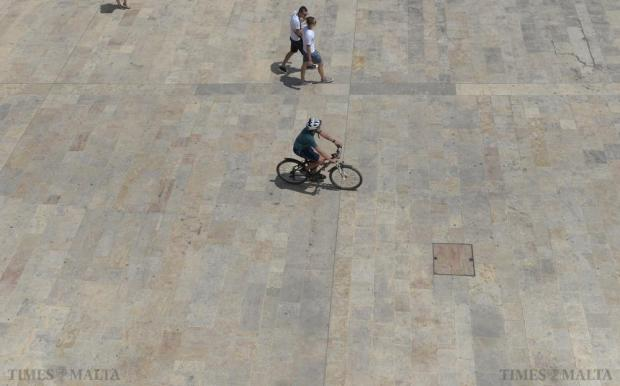 A man rides his bicycle through the entrance of Valletta on July 11. Photo: Matthew Mirabelli