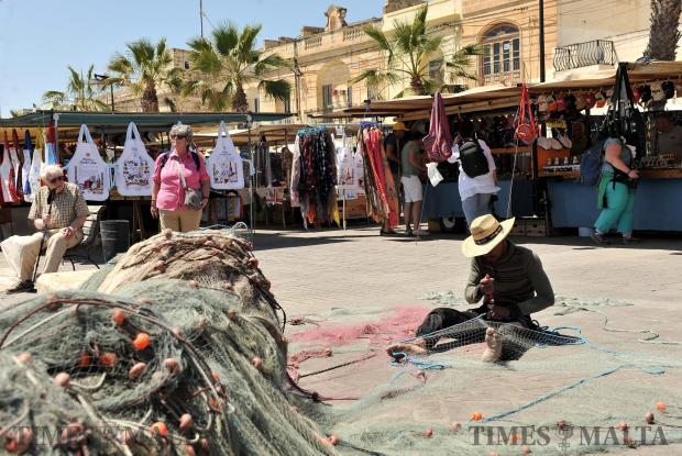 A man fixes fishing nets while a tourist looks on at Marsaxlokk on April 18. Photo: Chris Sant Fournier