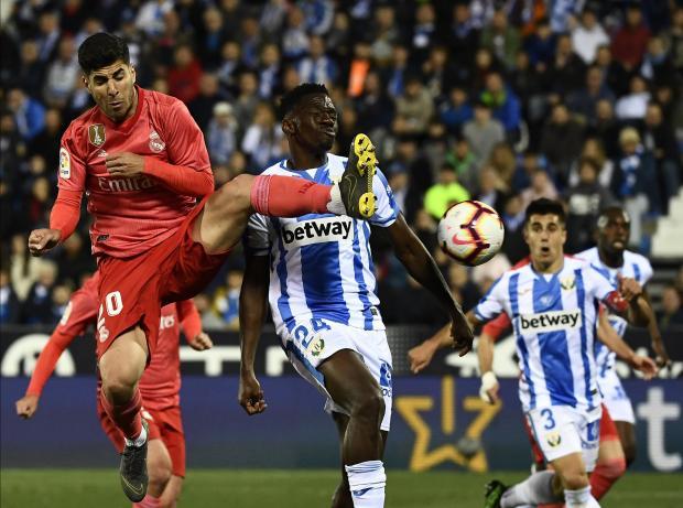 Real Madrid's Spanish midfielder Marco Asensio (R) challenges Leganes' Nigerian defender Kenneth Omeruo.