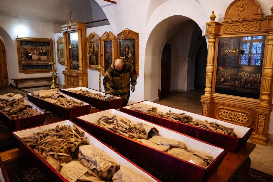 A municipal employee arranges coffins containing remains of Russian and French soldiers who died during Napoleon's 1812 retreat, in a small church in the monastery of John the Precursor in the town of Viazma.