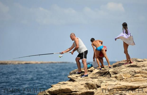 A man tries to catch a fish while curious children look on at Bugibba on August 24. Photo: Chris Sant Fournier