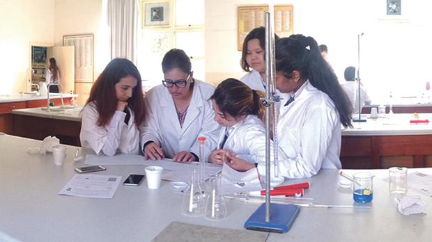 Teachers and students in St Edward College's chemistry lab.