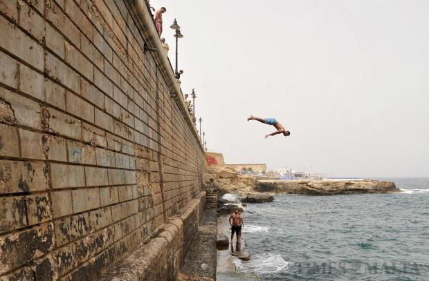 A group of young swimmers not put off by unstable weather, entertain passers by diving into the water from the Sliema promenade on May 11. Photo: Chris Sant Fournier