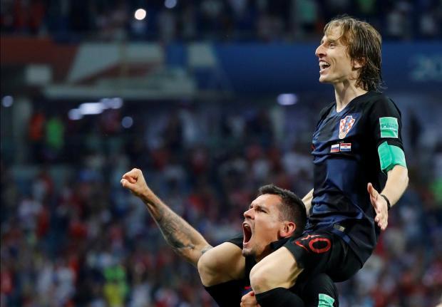 Luka Modric (top) celebrates Croatia's win with Dejan Lovren.