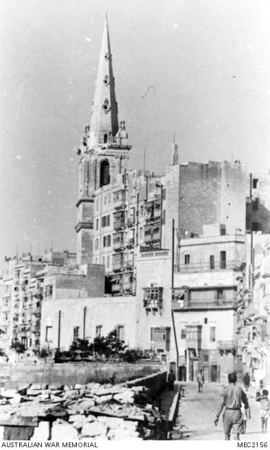 A shell strike and loss of stone-work at the top corner of the tower in 1943.