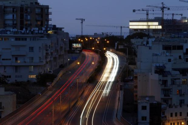 Vehicles make their way along Regional Road in St Julian's at dusk on May 19. Photo: Darrin Zammit Lupi