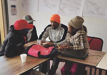 Four youth leaders from the Paballong Centre brainstorming ideas for the computer centre.