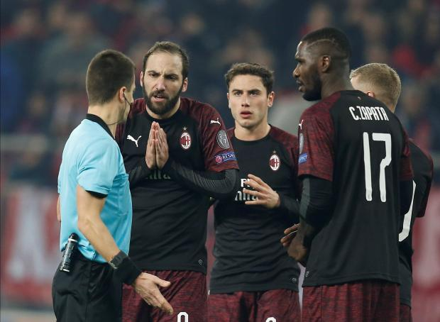 Milan's Gonzalo Higuain and team mates appeal to referee Benoit Bastien after he awarded a penalty to Olympiacos.
