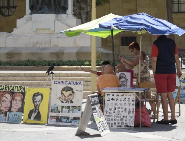 A Pigeon takes a rest on a tripod whilst an artist paints a boy in Valletta on August 29. Photo: Mark Zammit Cordina