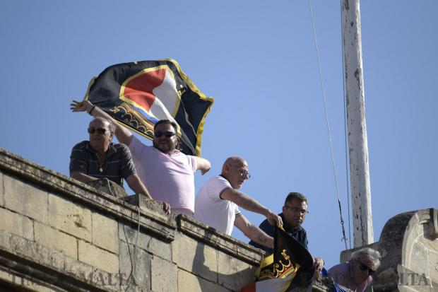 A man waves a Nationalist Party flag from a rooftop in Zabbar during a mass meeting on May 21. Photo: Mark Zammit Cordina