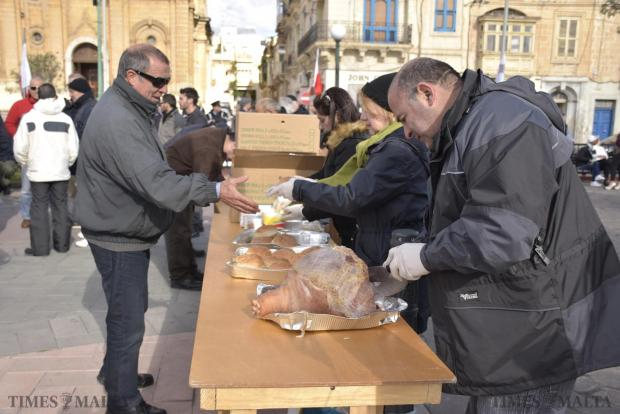 Members of the Ghaqda Patrijotti Maltin serve pork sandwiches during a protest in Msida on January 17, against a group of Muslims who have recently started using the square in front of the parish church for Friday prayers. Photo: Mark Zammit Cordina