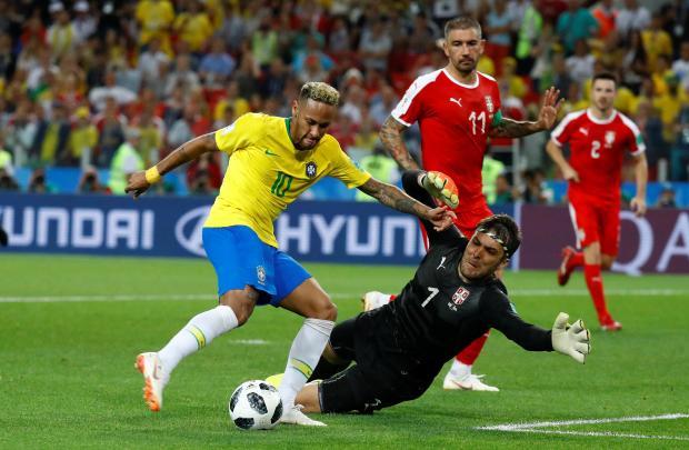 Serbia's Vladimir Stojkovic saves a shot from Brazil's Neymar.