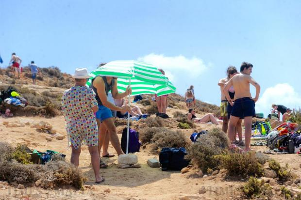 A tourist tries to mount an umbrella on the garrigue at the Blue Lagoon on Comino after MTA officials clamped down on beach operators overcrowding the area with deckchairs and umbrellas on August 17. Photo: Steve Zammit Lupi
