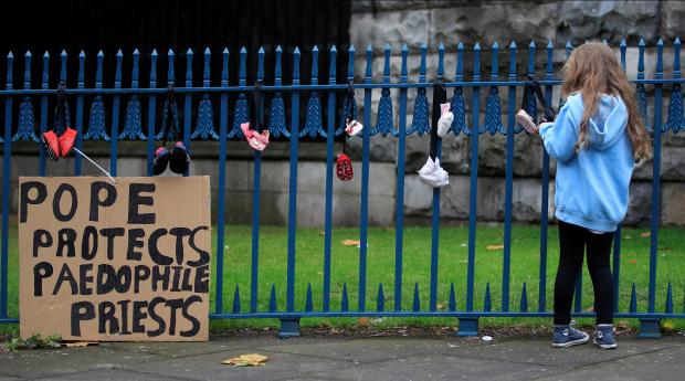 A young girl stands by a sign created by protesters opposed to the Pope's visit in Dublin. Photo: Reuters