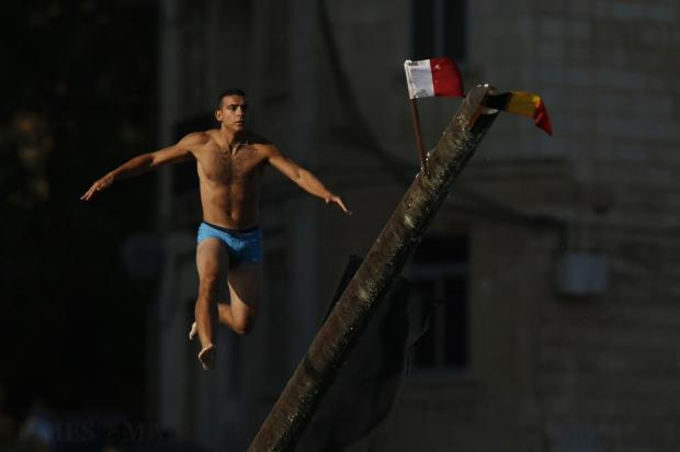 """A man slips off the """"gostra"""", a pole covered in grease, during the religious feast of St Julian, patron of the town of St Julian's, on August 28. In the traditional """"gostra"""", a game stretching back to the Middle Ages, young men, women and children have to make their way to the top and try to uproot one of the flags to win prizes. Photo: Darrin Zammit Lupi"""