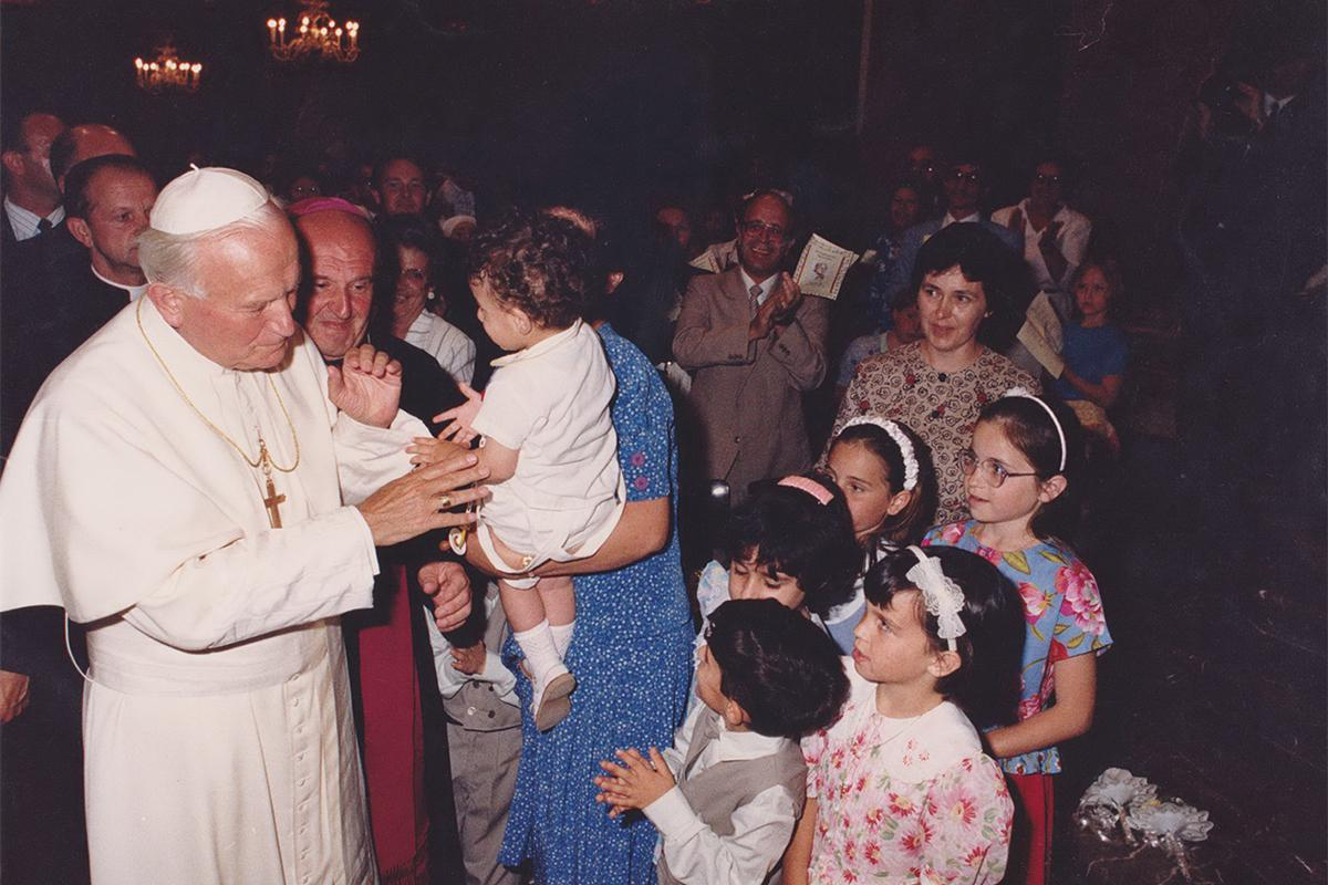 John Paul II blessing children and members of the congregation.