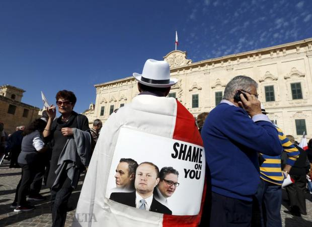 A protestor wears a Maltese flag and a Panama hat with a poster showing Prime Minister Joseph Muscat (centre) and two of his closest associates, Chief of Staff Keith Schembri (left) and Energy and Health Minister Konrad Mizzi (right) during a demonstration against alleged government corruption in Valletta on March 6. Both Schembri and Mizzi have come under relentless attack from opponents for allegedly opening secret Panama accounts shortly after taking office. Photo: Darrin Zammit Lupi
