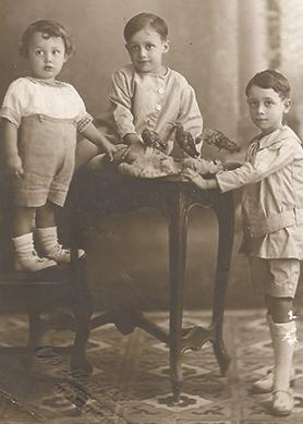 John Sladden (first from left, standing on a chair) together with his two eldest brothers Francis and Leo.