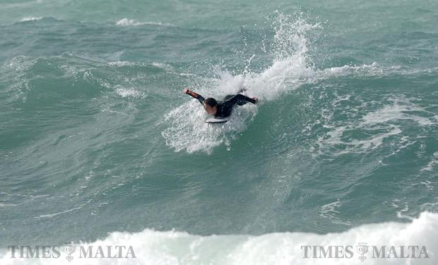 A surfer catches a large wave at Ghajn Tuffieha Bay on January 7. Photo: Matthew Mirabelli
