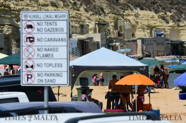 A gazebo is set up yards from a sign at Ġnejna Bay on August 6. Photo : Jonathan Borg