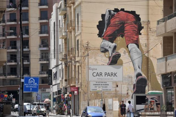 A large mural by graffiti artist MTO shows a man climbing through a hole into a building in Sliema on August 31. The man emerges from the other side in the continuation of the same art piece from the side of another building in the Italian town of Sapri. Photo: Chris Sant Fournier