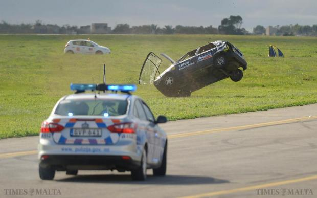 A stunt drive flips his car over after a simulated car chase at Paqpaqli Ghall-Istrina car show at Hal Farrug on December 7. Photo: Matthew Mirabelli