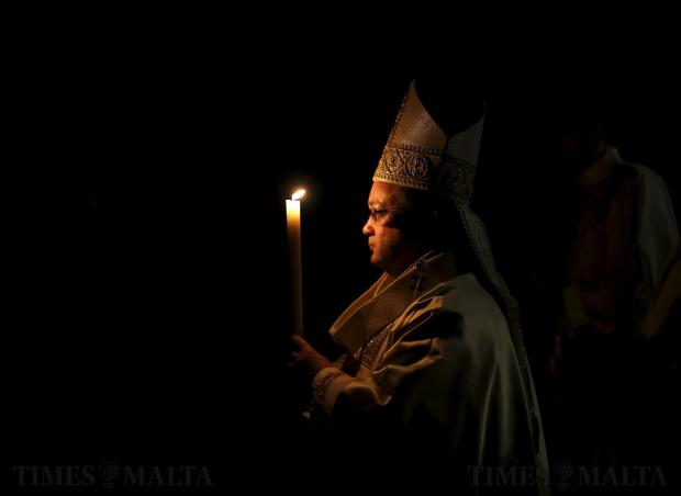 Archbishop Charles Scicluna carries a candle at the start of an Easter vigil mass at St John's Co-Cathedral in Valletta on March 26. Photo: Darrin Zammit Lupi