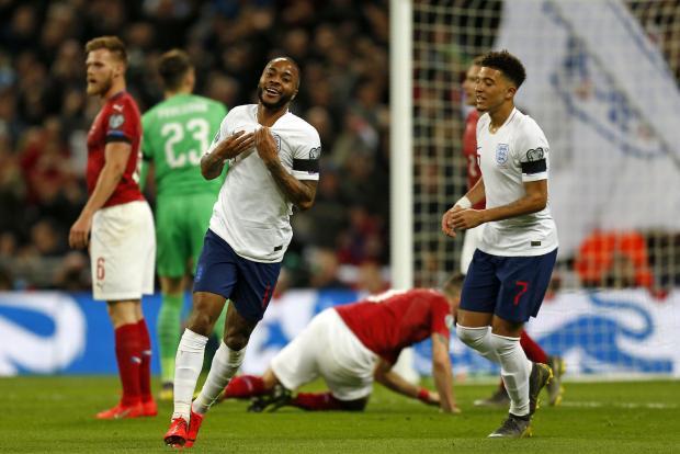 England's midfielder Raheem Sterling (centre) celebrates after scoring their third goal.