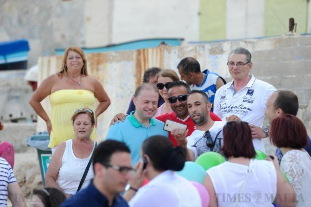 People pose for a selfie with Prime Minister Joseph Muscat as they wait for his wife Michelle to arrive in the Grand Harbour, after a three hour long swim for charity on June 25. Photo: Steve Zammit Lupi