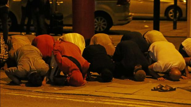 Men pray after the attack. Photo: Reuters