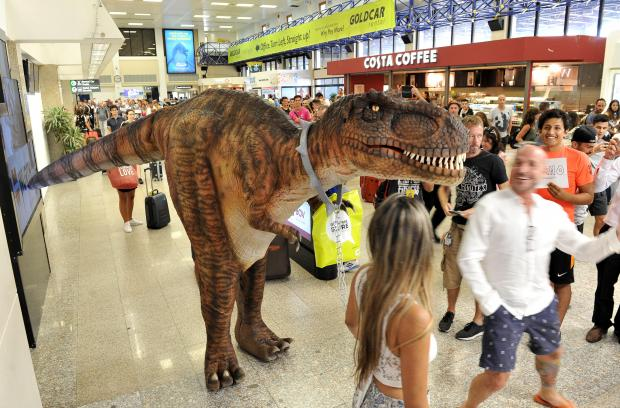Carrying a duty free shopping bag, Dino, the baby T-rex, makes it's way through the Arrivals Lounge at the Malta International Airport on July 26. Photo: Chris Sant Fournier