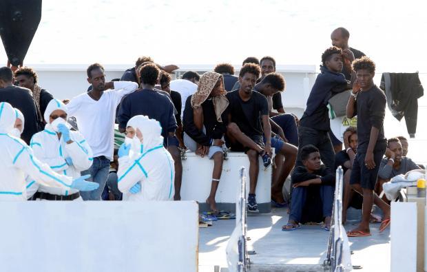 "Migrants wait to disembark from the Italian coast guard vessel ""Diciotti"" at the port of Catania."