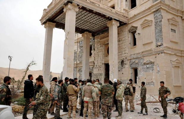 Forces loyal to Syria's President Bashar al-Assad gather at a palace complex on the western edge of Palmyra.