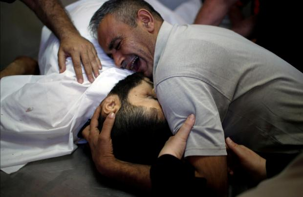 A man weeps over his brother's dead body. Photo: Reuters