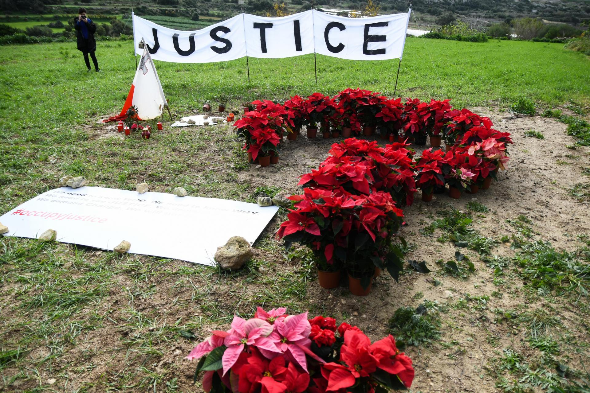 Flowers and a banner bearing the word 'justice' placed by civil society activists in Bidnija close to the site where Ms Caruana Galizia was murdered.