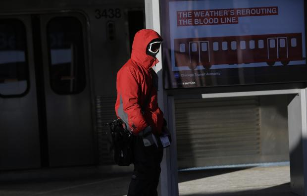 A commuter waits for the Red line train at the Belmont station.