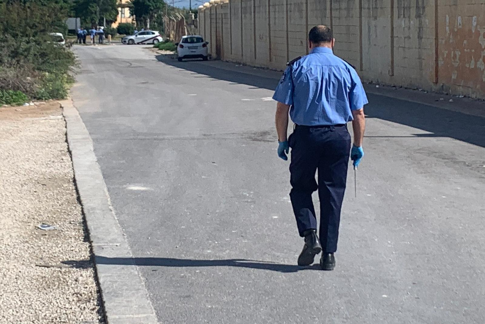 A police officer emerges from the open centre carrying a knife. Photo: Jonathan Borg