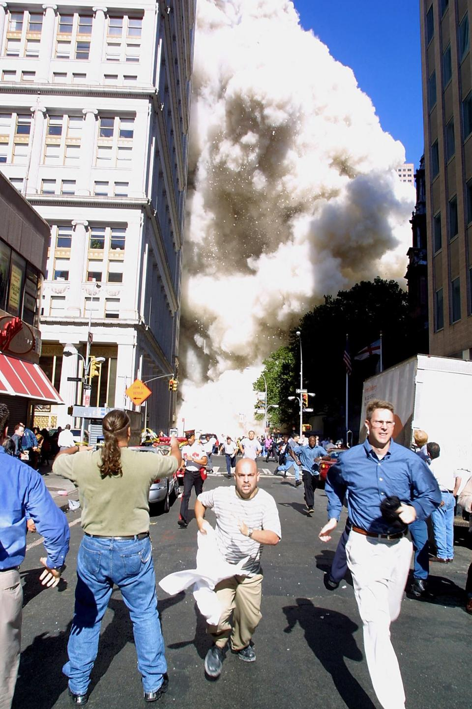 Pedestrians running from the scene as one of the World Trade Centre Towers in New York collapsed on September, 2001. Photo: Doug Kanter/AFP