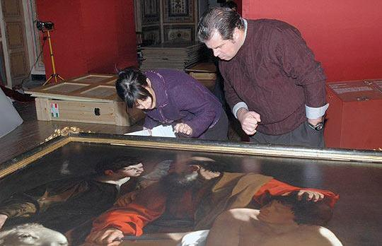 Visitors get a close look at one of the paintings on display during Heritage Malta's Caravaggio exhibition.