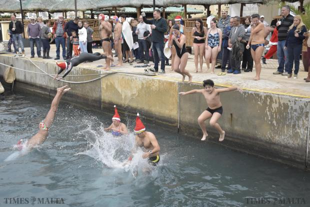 Participants jump into the sea for the fourth edition of Santa's Swim organized by the Grand Hotel Excelsior on December 5. Photo: Mark Zammit Cordina.