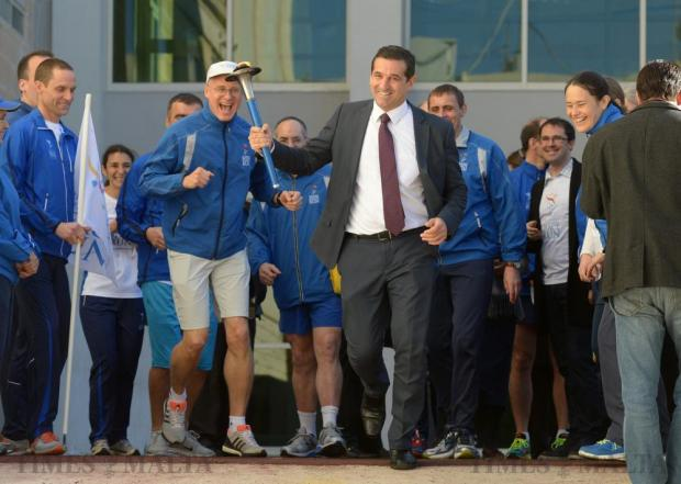 Parliamentary Secretary Chris Agius, runs with the Peace Torch at St Margaret Middle School in Cospicua after runners from the Sri Chinmoy Oneness-Home Peace Run visited the school on January 11.Photo: Matthew Mirabelli