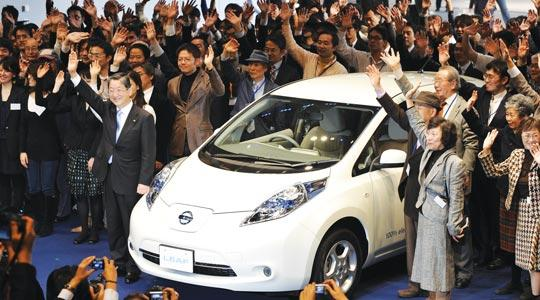 Nissan Motor Co. chief operating officer Toshiyuki Shiga, left, next to the vehicle, and customers posing for photographers during a press preview to announce the launch of the all-new Nissan Leaf electric vehicle at the company's headquarters in Yokohama, suburban Tokyo yesterday. Nissan said it will launch the Leaf, heralded as the world's first mass-produced electric vehicle, in Japan on December 20 and in the United States by the end of the month. Photo: Kazuhiro Nogi / AFP