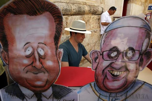 An artist draws caricatures of passers-by during the Colour Fest at the Valletta Waterfront on April 17. Photo: Darrin Zammit Lupi