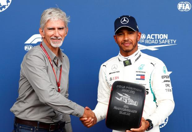 Lewis Hamilton (right) receives the pole position award from former driver Damon Hill.