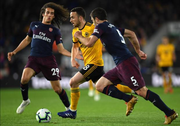 Wolves's Diogo Jota speeds past Arsenal defenders towards goal.
