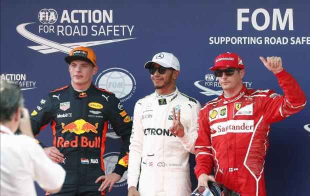 Mercedes' Lewis Hamilton reacts between Ferrari's Kimi Raikkonen and Redbull's Max Verstappen after getting pole position in qualifying.