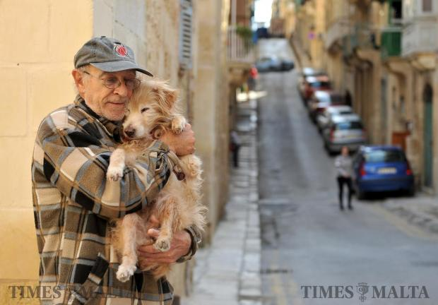 A man holds his pet dog Foffie which he rescued from the Valletta streets 14 years ago. March 1. Photo: Chris Sant Fournier