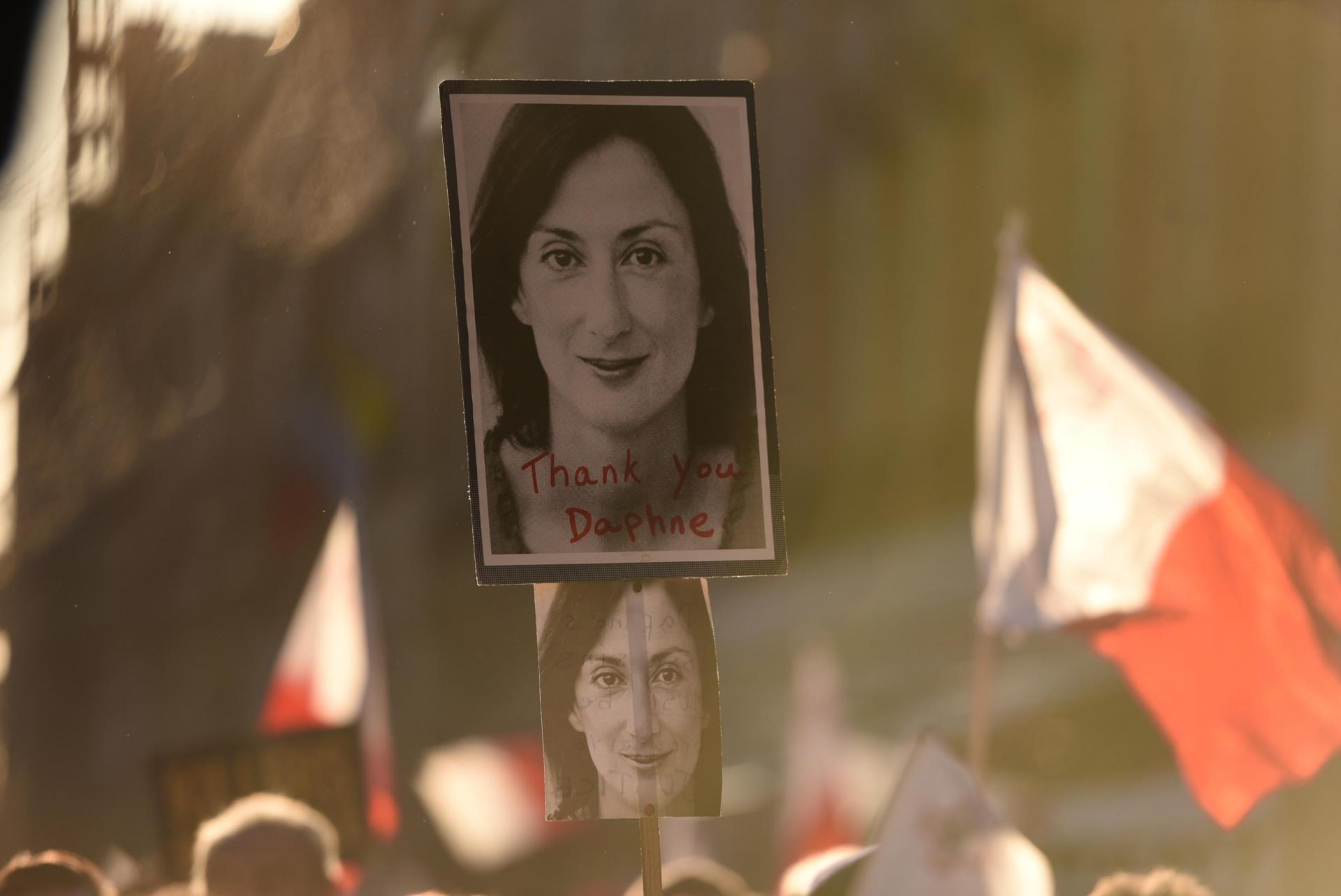 A banner thanking Daphne Caruana Galizia is held by a participant in a vigil commemorating her death.